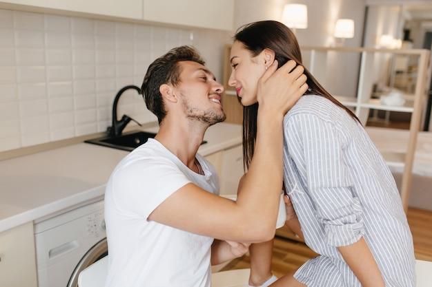 Gelooide man in witte kleren kussen brunette verlegen vrouw in mannelijk overhemd