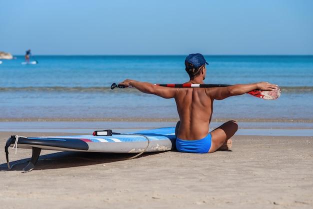 Gelooide man zit op het strand met een surfplank en riem en kijkt naar de zee.