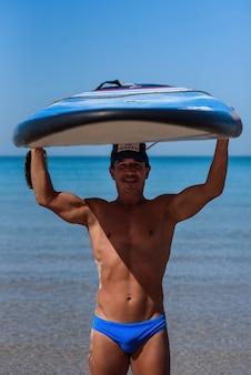 Gelooide sportieve man houdt zijn surfplank boven zijn hoofd op de zee.