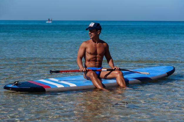 Gelooide sportieve man zit op zijn surfplank op het water en kijkt naar de zee.