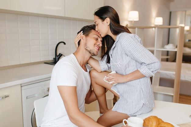 Gelooide vrouw in mannelijke overhemd zittend op tafel en kussen echtgenoot in voorhoofd