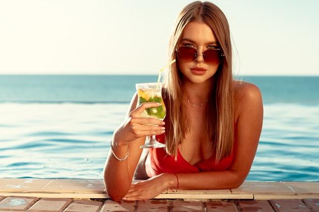 Gelooide vrouw in rode bikini in een zwembad met cocktail