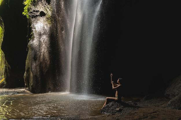 Geluiden van water. aantrekkelijk donkerbruin meisje dat in grot zit en watervalgeluid luistert, exotisch concept