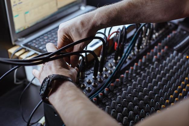 Geluidstechnicus die jack-audiokabel op studiomixer aansluit.