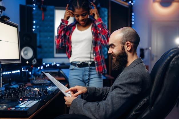 Geluidstechnicus en zangeres op afstandsbedieningspaneel in audio-opnamestudio.