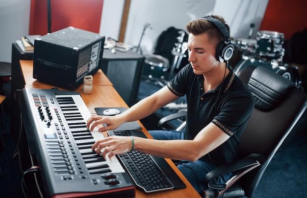 Geluidstechnicus in koptelefoon die binnen in de studio werkt en muziek mixt.