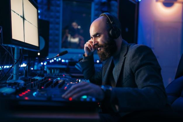 Geluidstechnicus in koptelefoon luistert samenstelling van zangeres in opnamestudio.