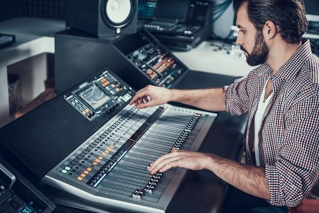 Geluidstechnicus met behulp van studio mengtafel.