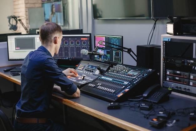 Geluidstechnicus werken in studio met apparatuur