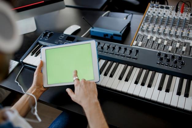 Geluidstechnicus werkt aan mengpaneel in de opnamestudio en houdt een tablet vast