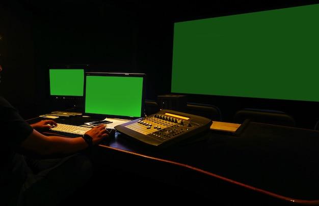 Geluidstechnicus werkzaam in postproductiestudio voor digitale audio- en videobewerking groen scherm