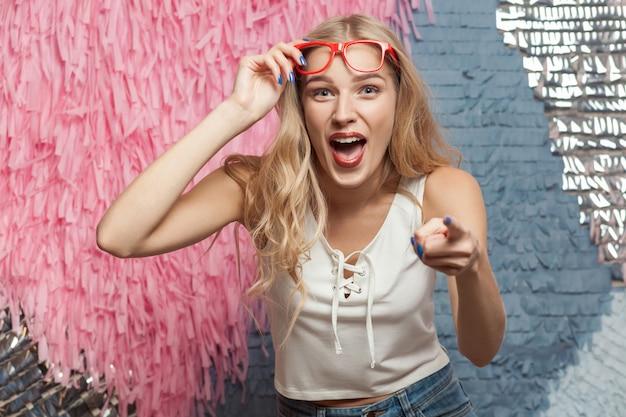 Geluk blond meisje in rode bril wijzende vinger en brede glimlach