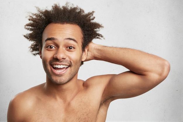 Geluk concept. blij dat positieve afro-amerikaanse man met trendy kapsel naakt poseert