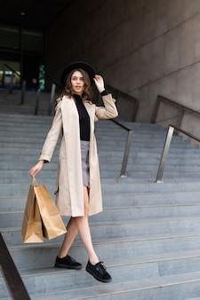 Geluk, consumentisme, verkoop en mensenconcept - glimlachende jonge vrouw met boodschappentassen over wandelgalerijmuur