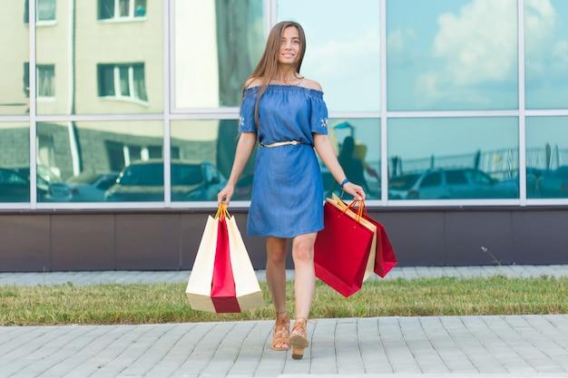 Geluk, consumentisme, verkoop en mensenconcept - glimlachende jonge vrouw met boodschappentassen