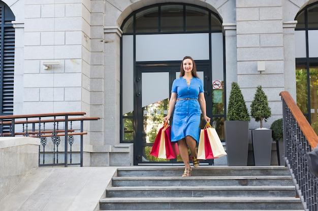 Geluk, consumentisme, verkoop en mensenconcept. lachende jonge vrouw met boodschappentassen