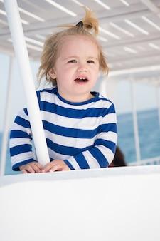 Geluk en jeugd. kleine gelukkige babyjongen of schattig kind op boot witte kleur met blond haar in gestript marine shirt op zonnige natuurlijke achtergrond. nautische mode voor kinderen