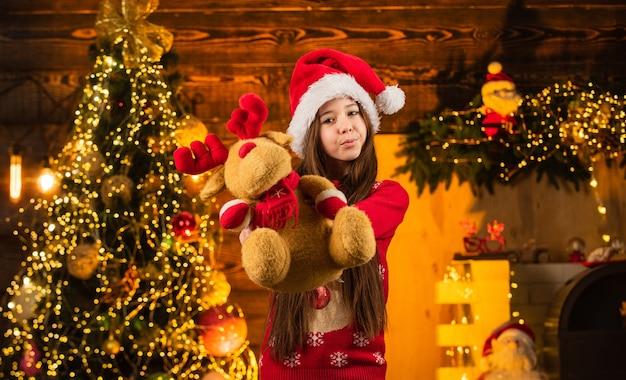 Geluk en vreugde. kind blij opgewonden meisje vindt geschenken in de buurt van kerstboom. vrolijk kerstfeest. gelukkig kindertijdconcept. kerstmuts voor kinderen. de kerstman bracht cadeautjes. tijd voor wonderen. alles wat ik wil voor kerst.