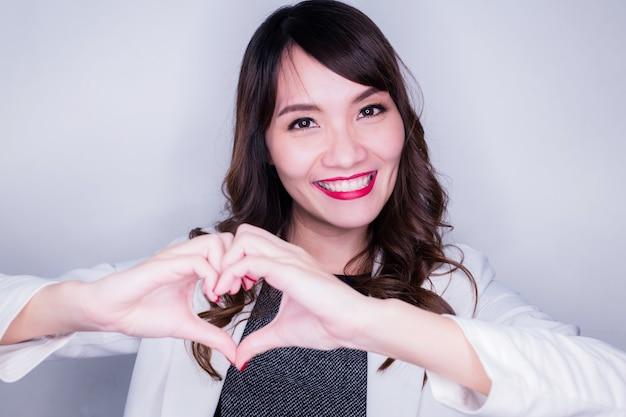 Geluk en vreugdevolle aziatische vrouw met hand maken hart vorm teken betekenen liefde concept