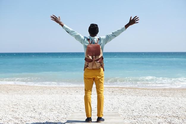 Geluk en vrijheid. mensen en reizen. onherkenbare reiziger met donkere huid en rugzak die uitgestrekte armen opheft terwijl hij alleen staat op de brede promenade op het strand, terwijl hij de schoonheid om hem heen probeert te omarmen