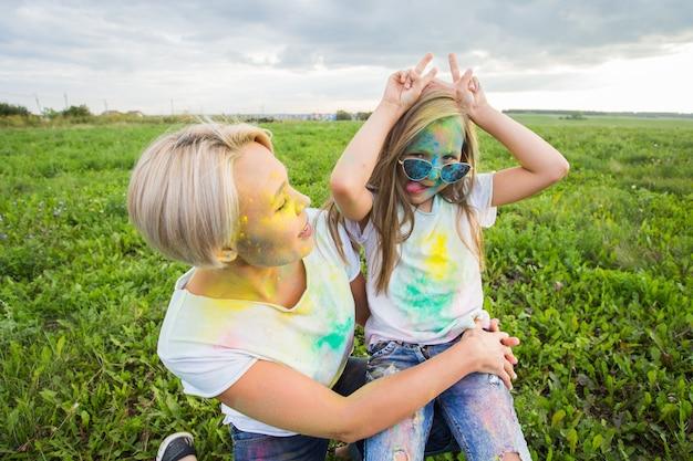 Geluk, holi festival en vakantie concept - moeder en haar dochter bedekt met kleur poeder glimlachen