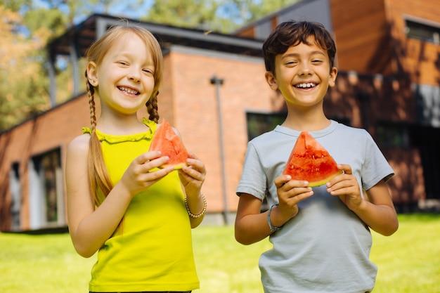 Geluk in ons. vrolijke charmante kinderen glimlachen en eten een rijpe watermeloen