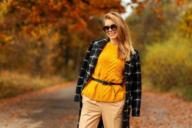 Geluk jong meisje met glimlach in mode jas en gele vintage trui met zonnebril wandelingen in herfst park met kleurrijke bladeren