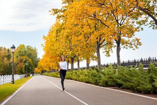 Geluk jong volwassen meisje joggen in herfst park, camera kijken en brede glimlach. buitenshuis