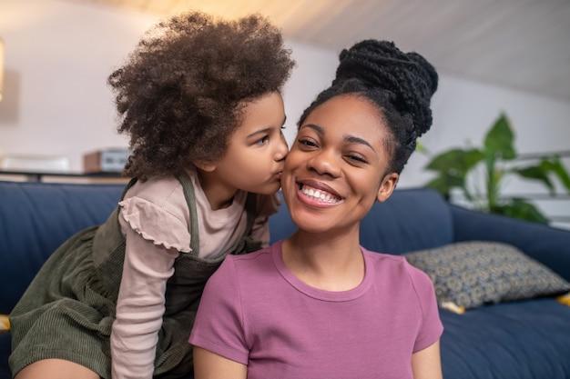 Geluk. klein schattig meisje met een donkere huid die een gelukkige glanzende jonge moeder op de wang kust in een gezellige kamer
