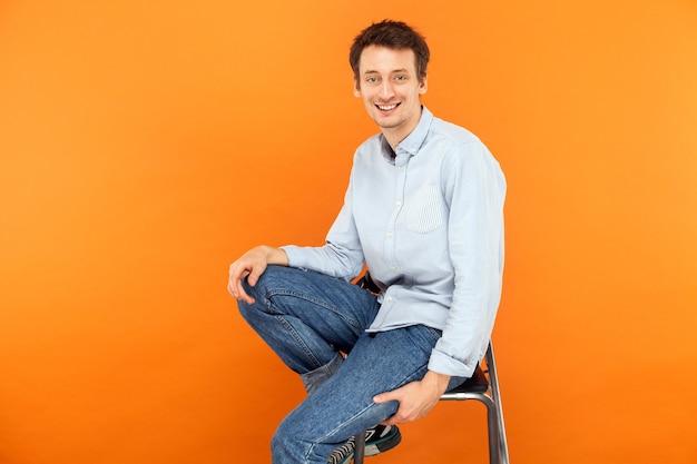 Geluk man zit op stoel kijkend naar camera en brede glimlach