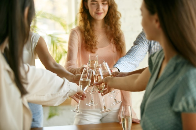 Geluk. mensen rammelende glazen met wijn of champagne.