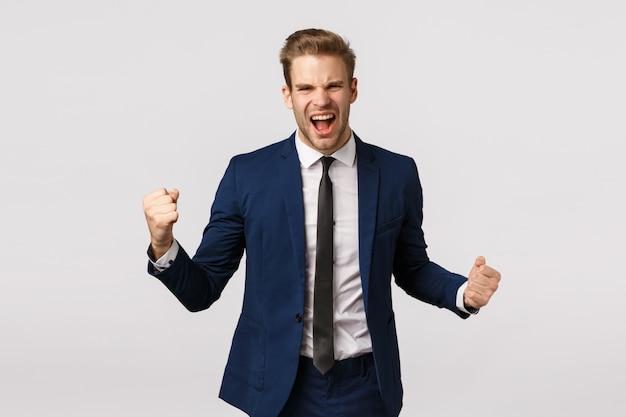 Geluk, prestatie en bedrijfsconcept. knappe zelfverzekerde en triomferende jonge zakenman verdiende veel geld, ondertekende deal, balde vuisten en schreeuwende kampioen, voel zich vrolijk, witte achtergrond