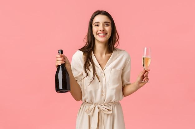 Geluk, romantiek en liefde concept. elegante prachtige glimlachende, gelukkige vrouw viert verjaardag, valentijnsdag, houdt fles champagne en glas, genietend van drankje en hef glas voor gelegenheid
