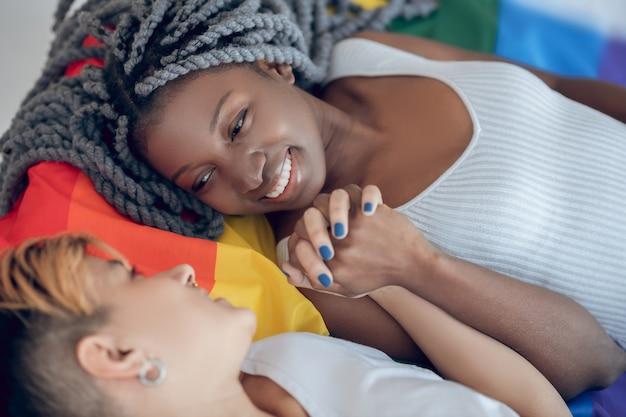 Geluk. twee jonge meisjes met een regenboogvlag die aan elkaar glimlachen