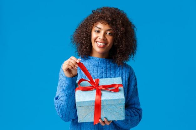 Geluk, vakantie en familieconcept. gelukkige glimlachende charmante afrikaans-amerikaanse vrouw met afrokapsel, het uitpakken van gift, het trekken van knoop en het glimlachen vrolijk ontvangend heden op nieuw jaar