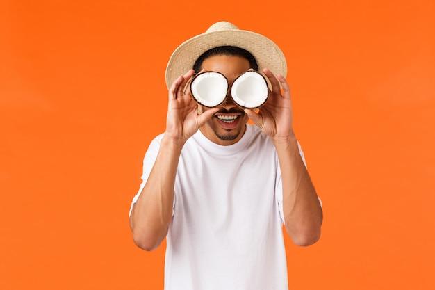 Geluk, vakantie en toerismeconcept. grappige zorgeloze afro-amerikaanse man in wit t-shirt, zomerhoed, kokosnoten op ogen houdend en glimlachend geamuseerd, gek rond, staande oranje