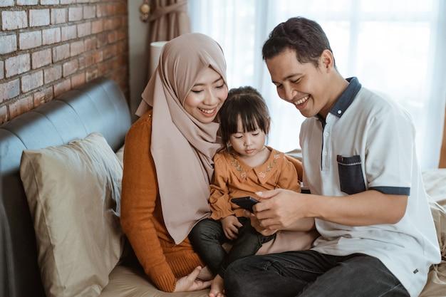 Geluk van een moslimfamilie samen bij gebruik van een smartphone