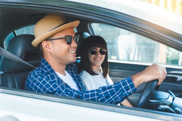 Geluk van het zijaanzicht het jonge aziatische paar en het glimlachen zitting in auto. reisconcept, veiligheidsconcept eerste verzekering
