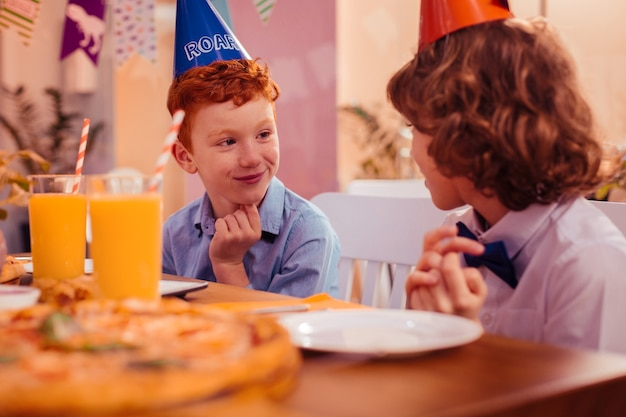 Geluk voelen. vrolijke jongen die een glimlach op zijn gezicht houdt terwijl hij naar zijn gesprekspartner kijkt