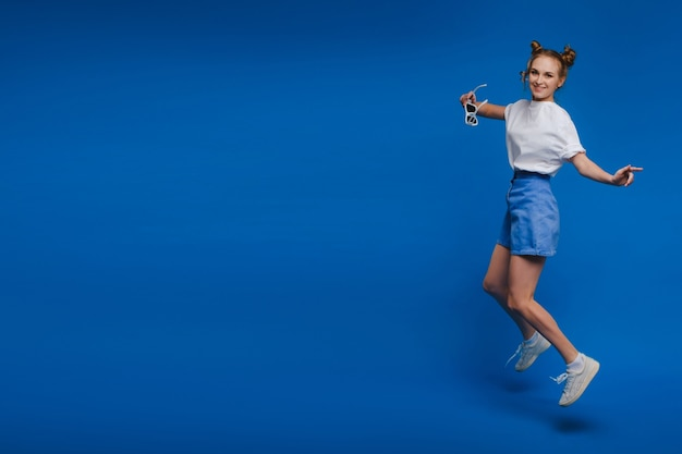Geluk, vrijheid, beweging en mensenconcept - glimlachende jonge vrouw die in lucht over witte achtergrond springt.