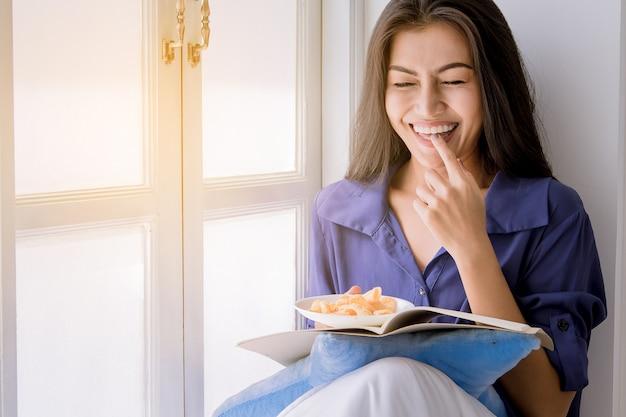 Geluk vrouw geniet van het eten van chips tijdens het lezen van een boek naast het venster.