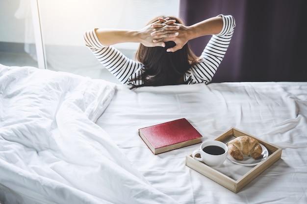 Geluk vrouw op het bed met oud boek en 's morgens kopje koffie en croissant