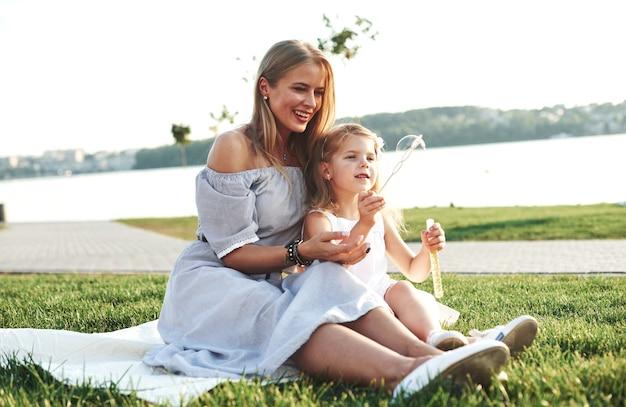 Geluk zit in kleine dingen. foto van jonge moeder en haar dochter die goede tijd hebben op het groene gras met meer bij achtergrond.