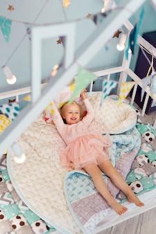 Gelukkig 3-jarige meisje draagt roze jurk liggend op gezellige bed naar beneden. bovenaanzicht. uitzicht van boven