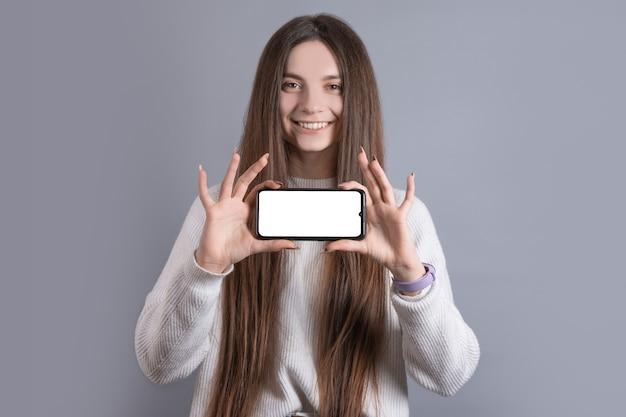Gelukkig aantrekkelijk donkerbruin vrouwenmeisje in sweater die de smartphonescherm van de greep het lege telefoon tonen. kijkend naar de camera en glimlach over grijze achtergrond.