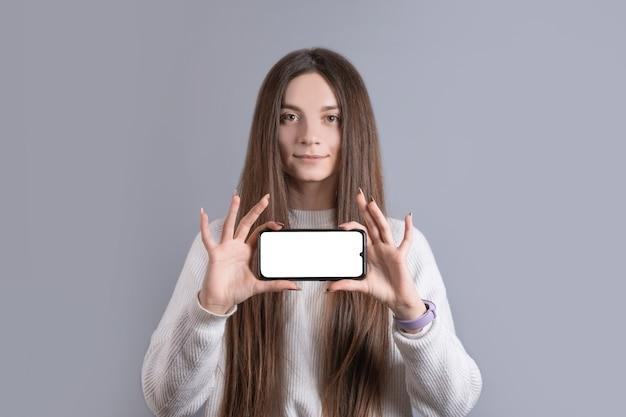 Gelukkig aantrekkelijk donkerbruin vrouwenmeisje in sweater die de smartphonescherm van de greep het lege telefoon tonen.