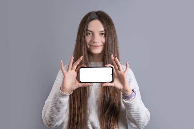 Gelukkig aantrekkelijk donkerbruin vrouwenmeisje in sweater die de smartphonescherm van de greep het lege telefoon tonen