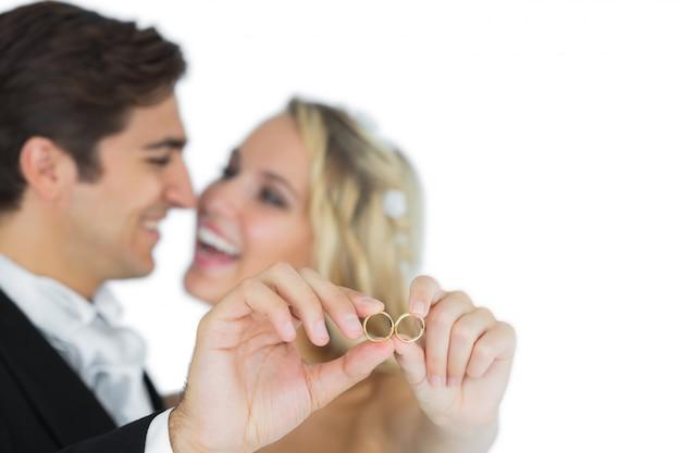 Gelukkig aantrekkelijk echtpaar toont hun trouwringen