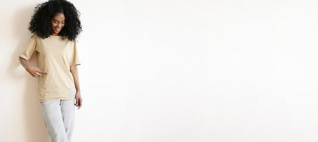 Gelukkig aantrekkelijk jong afrikaans meisje met afro-kapsel gekleed in blanco oversized t-shirt, vinger erop wijzend en vrolijk glimlachend