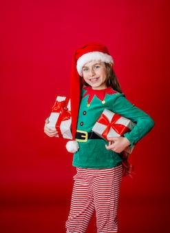 Gelukkig aantrekkelijk meisje met geschenken in een kostuum van santa claus helper elf op een fel rood